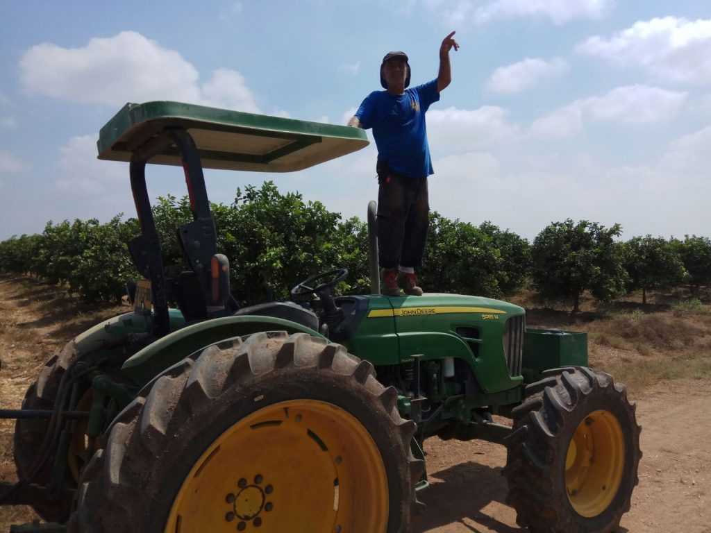 A farmer-standing-on-a-tractor